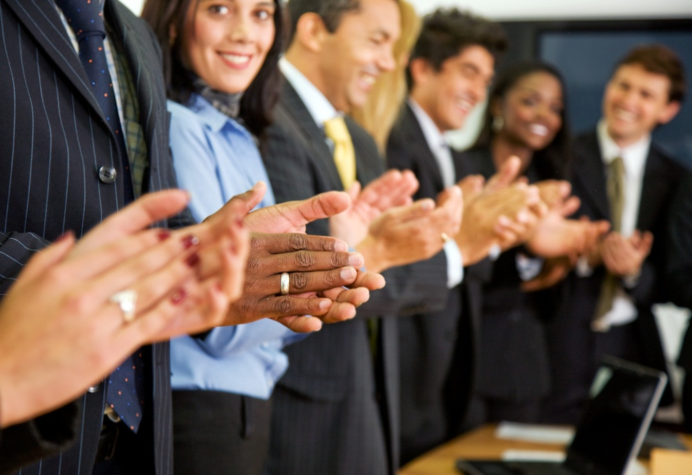 business team clapping in an office facing the camera.jpeg